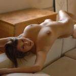 Красотка с большой грудью лежит на спинке дивана