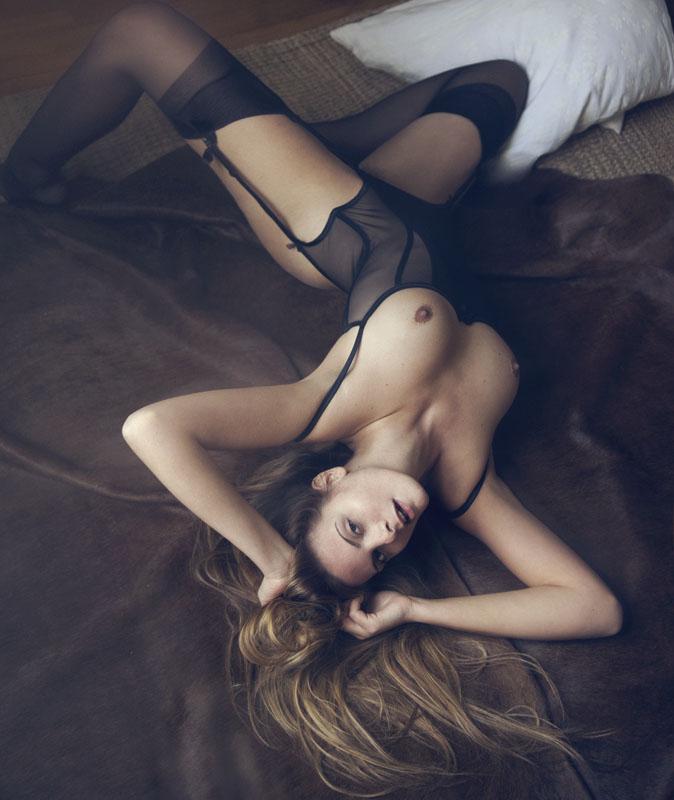 Красотка с большой грудью лежит на шелковом одеяле