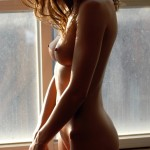 Милая брюнеточка возле окна