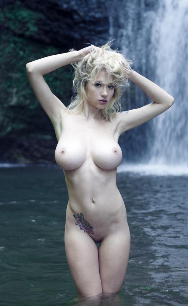 Девушка показывает огромные дойки на фоне водопада